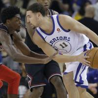 Golde State's Klay Thompson carries the ball as Chicago's Justin Holiday defends during the Warriors' 143-94 win on Friday. | AP