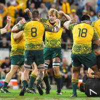 Australia players celebrate after beating New Zealand in Brisbane on Oct. 21. | KYODO
