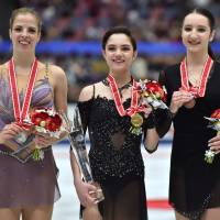 Russia's Evgenia Medvedeva (center), the NHK Trophy women's champion, poses with second-place finisher Carolina Kostner of Italy (left) and Russia's Polina Tsurskaya, who placed third, during an award ceremony on Saturday in Osaka. | AFP-JIJI