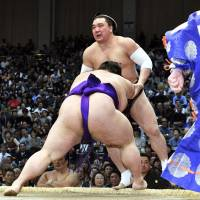 Takakeisho (front) pushes Harumafuji out of the ring at the Kyushu Grand Sumo Tournament in Fukuoka on Monday. | KYODO