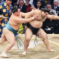 Maegashira Tamawashi (left) defeats ozeki Takayasu on Thursday, his 33rd birthday, at the Kyushu Grand Sumo Tournament in Fukuoka. | KYODO