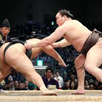 Hakuho (right) gets to grips with Chiyonokuni at the Kyushu Grand Sumo Tournament in Fukuoka on Monday. | KYODO