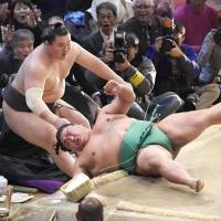 Hakuho (left) and Yoshikaze fall out of the ring during their bout at the Kyushu Grand Sumo Tournament on Wednesday in Fukuoka. | KYODO