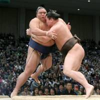 Hakuho shoves Mitakeumi out of the raised ring on Thursday at the Kyushu Grand Sumo Tournament. | KYODO