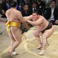 Hakuho overpowers No. 9 maegashira Endo on Saturday at the Kyushu Grand Sumo Tournament. Hakuho improved to 13-1. | KYODO