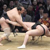 Aminishiki (left) competes against Chiyoshoma on the final day of the Kyushu Grand Sumo Tournament on Sunday in Fukuoka. | KYODO