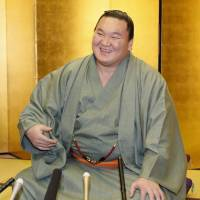 Hakuho smiles during a news conference in Fukuoka on Monday. | KYODO
