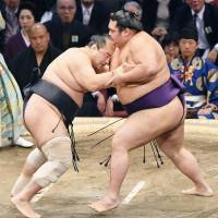 Daiamami (right) competes against Aminishiki on the fifth day of the Kyushu Grand Sumo Tournament on Nov. 16 in Fukuoka. | KYODO