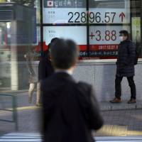 A man walks past an electronic stock board showing the Nikkei 225 index at a securities firm in Tokyo on Wednesday. | AP