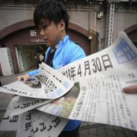 Extra editions of a newspaper reporting the date of Emperor Akihito's abdication are handed out near Shinbashi Station in Tokyo on Friday. | AP