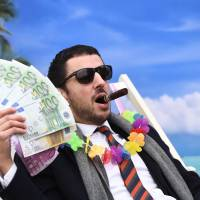 An Oxfam activist stages a satirical street-play mimicking a wealthy person hidding his money in a tax haven, on Tuesday near the European institutions in Brussels, where a meeting of European Union ministers is ongoing over a credible blacklist of non-EU tax havens. The EU has struggled for over a year to finalize the blacklist, with smaller, low-tax EU nations such as Ireland, Malta and Luxembourg worried about scaring off multinationals. | AFP-JIJI