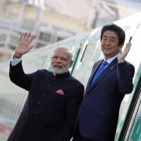 Prime Minister Shinzo Abe and Indian Prime Minister Narendra Modi wave after leaving a shinkansen bullet train during a visit to a plant owned by Kawasaki Heavy Industries Ltd.'s Rolling Stock Co. in Kobe, Hyogo Prefecture, in November last year. | BLOOMBERG