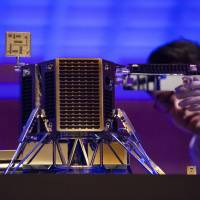 An employee looks at a concept model of Ispace Inc.'s lunar lander during a news conference in Tokyo on Wednesday. Tokyo-based Ispace said it raised ¥10.2 billion from some of the country's biggest businesses, including Japan Airlines Co. and Tokyo Broadcasting System Holdings Inc. | BLOOMBERG