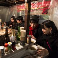 Customers eat at a mobile food stall in the Tenjin area of Fukuoka Prefecture on Dec. 21. Fukuoka is expanding production of a locally developed variety of grain that's designed to be perfect for tonkotsu ramen, a dish of cloudy white pork broth with noodles and slices of pork that originates in the region. | BLOOMBERG