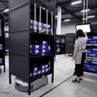 An employee types on a touch screen as a Geek Inc. Eve robot transports shelves at Acca International Co. warehouse in Inzai, Chiba Prefecture, on Sept. 7. | BLOOMBERG