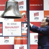 Sharp Corp. President and CEO Tai Jeng-wu rings a bell at a ceremony to mark the company's return to the Tokyo Stock Exchange's first section on Thursday. | KYODO