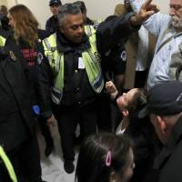 Bekah Bailey (right) of Minneapolis is warned by a Capitol Police officer of arrest unless she and others move on from a hallway where they were protesting the Republican tax overhaul bill Tuesday on Capitol Hill in Washington. | AP