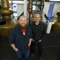 Matt Hofmann (left), the Master Distiller at Westland Distillery, and Steven Hawley, director of marketing, pose for an October photo in the still room of the distillery in Seattle, where Westland is making a whiskey using smoke from peat grown locally in Washington state. | AP