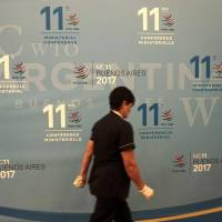A worker walks past a banner Sunday at the 11th Ministerial Conference of the World Trade Organization in Buenos Aires, Argentina. | AFP-JIJI