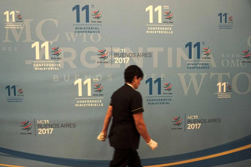A worker walks past a banner Sunday at the 11th Ministerial Conference of the World Trade Organization in Buenos Aires, Argentina.   AFP-JIJI