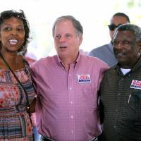 Democratic Alabama U.S. Senate candidate Doug Jones stand between two supporters while campaigning at an outdoor festival in Grove Hill, Alabama, on Nov. 4. | REUTERS