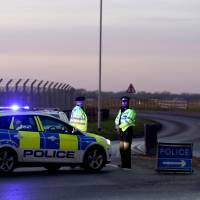 British police stand guard at the entrance to the U..S Air Force base at RAF Mildenhall, Suffolk, Britain, Monday. | REUTERS