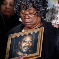 Judy Scott looks over a photo of her son, Walter Scott, during a news conference after former police officer Michael Slager was sentenced to 20 years in prison, in Charleston, South Carolina, Thursday. | REUTERS