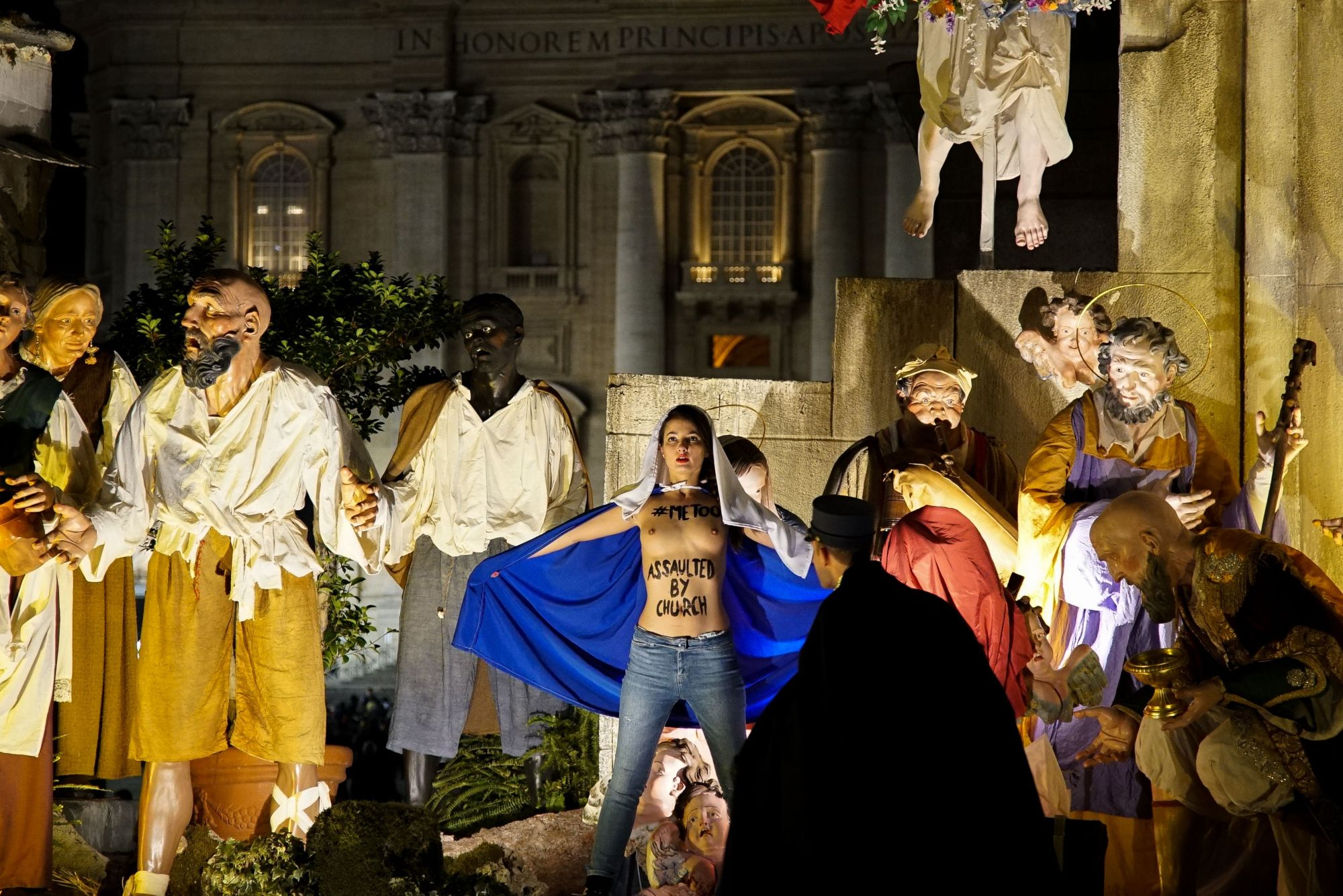 A handout picture taken Sunday and released on Monday by the Femen group shows a police officer running toward a Femen activist standing topless in front of the Nativity scene in Saint Peter's square at the Vatican. | FEMEN / VIA AFP-JIJI