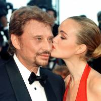 French singer Johnny Hallyday is kissed by his wife Laeticia as they arrive for the opening of the 51st Cannes Film Festival in Cannes, France, in 1998.   REUTERS