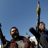 Tribesmen loyal to the Houthi movement hold their weapons as they attend a gathering to mark 1,000 days of the Saudi-led military intervention in the Yemeni conflict, in Sanaa Thursday. | REUTERS