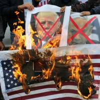 Palestinians burn posters depicting Israeli Prime Minister Benjamin Netanyahu and U.S. President Donald Trump during a protest over the U.S. intention to move its embassy to Jerusalem and to recognize the city of Jerusalem as the capital of Israel, in Rafah in the southern Gaza Strip, Wednesday. | REUTERS