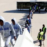 Guinean migrants get on a plane to be deported to Guinea, in Misrata, Libya, Wednesday. | REUTERS