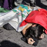 An activist, covered with a Mexican flag and posing as a homicide victim, lies on the ground during a demonstration against the approval of an internal security law that will grant surveillance powers to the army at Paso del Norte International Bridge in Ciudad Juarez, Mexico, on Dec. 16. The bridge links Mexico and the United States. | AFP-JIJI