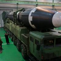 North Korean leader Kim Jong Un is seen next to a newly developed Hwasong-15 intercontinental ballistic missile in this undated photo released Thursday. | REUTERS