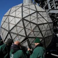 Workers install Waterford Crystal triangles on the Times Square New Year's Eve Ball on the roof of One Times Square in Manhattan, New York, Wednesday.   REUTERS