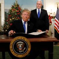 U.S. Vice President Mike Pence stands by as U.S. President Donald Trump signs a proclamation that states the United States recognizes Jerusalem as the capital of Israel and will move its embassy there, during an address from the White House in Washington Wednesday. | REUTERS