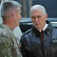 U.S. Vice President Mike Pence chats with General Nick Nicholson, commander of U.S. forces in Afghanistan, while posing with military leaders shortly after arriving at Bagram Air Field in Afghanistan on Thursday. | REUTERS