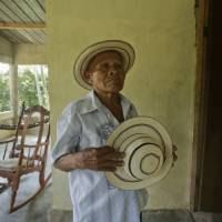 Pasion Gutierrez holds a finished traditional pintao hat at his home in El Jaguito, Panama. | AP