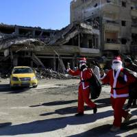 Men dressed in Santa Claus costumes walk past destroyed buildings in the eastern Syrian city of Raqqa on Tuesday. A U.S.-backed offensive ousted the Islamic State group from Raqqa in October but the city has been left ravaged by fighting, and only a small percentage of its prewar population has returned as the year draws to a close. | AFP-JIJI