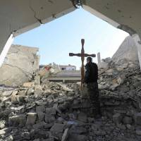 A member of the Syrian Arab-Kurdish forces places a cross in the rubble ahead of a Christmas celebration at the heavily damaged Armenian Catholic Church of the Martyrs in the city center of the eastern Syrian city of Raqqa on Tuesday following a mine clarence operation at the site a few days earlier. | AFP-JIJI