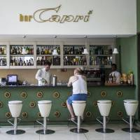 A customer sits at the lobby bar of the Hotel Capri in Havana in September. The U.S. says 24 government officials and spouses fell ill starting last year due to invisible attacks in homes and later in some hotels. | AP