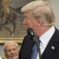 Former Astronaut Buzz Aldrin listens as U..S President Donald Trump speaks during a signing ceremony for Space Policy Directive 1, with the aim of returning Americans to the moon, in the Roosevelt Room at the White House in Washington Monday. | AFP-JIJI
