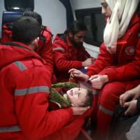 Syrian staff from the International Committee of the Red Cross evacuate a baby in Douma in the eastern Ghouta region on the outskirts of the capital Damascus on Tuesday. Aid workers have begun evacuating emergency medical cases from Syria's besieged rebel bastion of eastern Ghouta, the International Committee of the Red Cross said. | AFP-JIJI