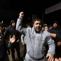 Palestinians react during a protest over U.S. President Donald Trump's decision to recognize Jerusalem as Israel's capital, in Khan Younis in the southern Gaza Strip Wednesday. | REUTERS