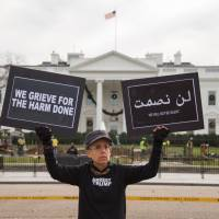 A protester displays her signs in front of the White House as U..S President Donald Trump announces his decision on the status of Jerusalem on Wednesday in Washington. | AFP-JIJI