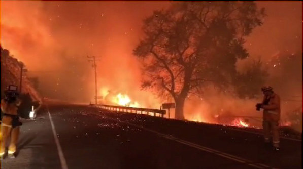 A man takes pictures of wildfires from a highway in Ojai, California, Thuesday in this picture obtained from social media. | INSTAGRAM @EPN106 / VIA REUTERS