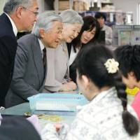 Emperor Akihito and Empress Michiko visit disabled workers at a Tokyo department store on Friday, the day the Cabinet formally approved the Emperor's abdication date of April 30, 2019. | KYODO