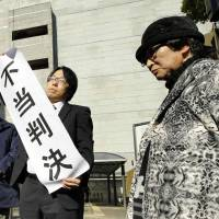 Chiyoko Iwanaga, leader of the plaintiffs in a Nagasaki hibakusha-recognition case, stands in front of the Supreme Court on Monday after the court's ruling. | KYODO