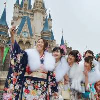 Kimono-clad women take a group selfie at Tokyo Disneyland in Chiba Prefecture during a coming-of-age ceremony on Jan. 9. The government plans to introduce a bill to the Diet next month to lower the age of majority from 20 to 18. | KYODO