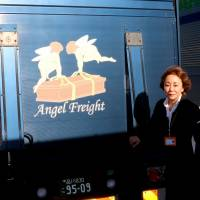 Airhearse International Inc. President Rie Kimura stands next to the company's Angel Freight logo, which appears on the rear door of a truck used as a preparation site for bodies, in the cargo area at Haneda airport in Tokyo on Oct. 23. | KYODO